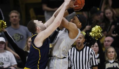 California center Kameron Rooks, left, blocks a shot by Colorado guard George King in the first half of an NCAA college basketball game Saturday, March 4, 2017, in Boulder, Colo. (AP Photo/David Zalubowski)