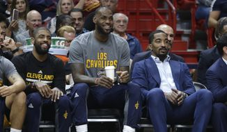 Cleveland Cavaliers' Kyrie Irving, left, LeBron James, center, and J.R. Smith, right, watch from the bench during the first half of an NBA basketball game against the Miami Heat, Saturday, March 4, 2017, in Miami. (AP Photo/Lynne Sladky)