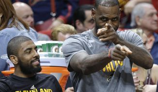 Cleveland Cavaliers' LeBron James, right, gestures as he sits with Kyrie Irving, left, on the bench during the first half of an NBA basketball game against the Miami Heat, Saturday, March 4, 2017, in Miami. (AP Photo/Lynne Sladky)