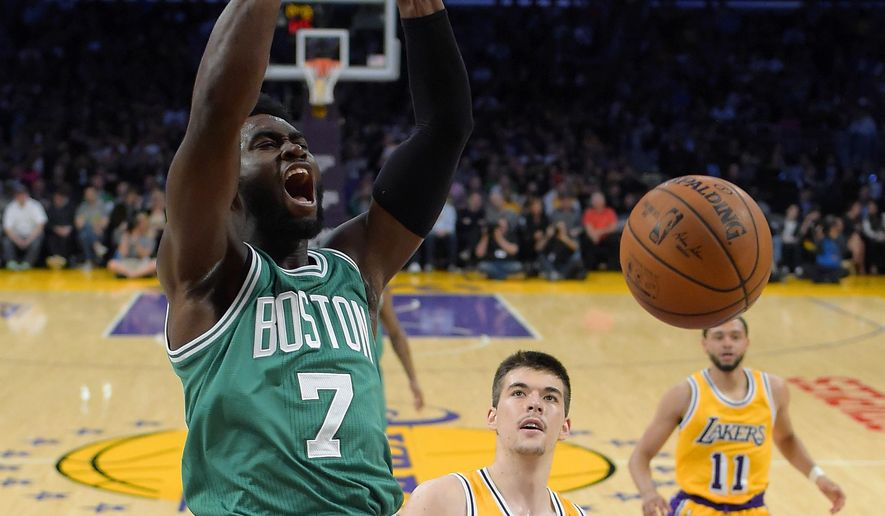 Boston Celtics forward Jaylen Brown, left, dunks as Los Angeles Lakers center Ivica Zubac, center, and guard Tyler Ennis watch during the first half of an NBA basketball game, Friday, March 3, 2017, in Los Angeles. (AP Photo/Mark J. Terrill)