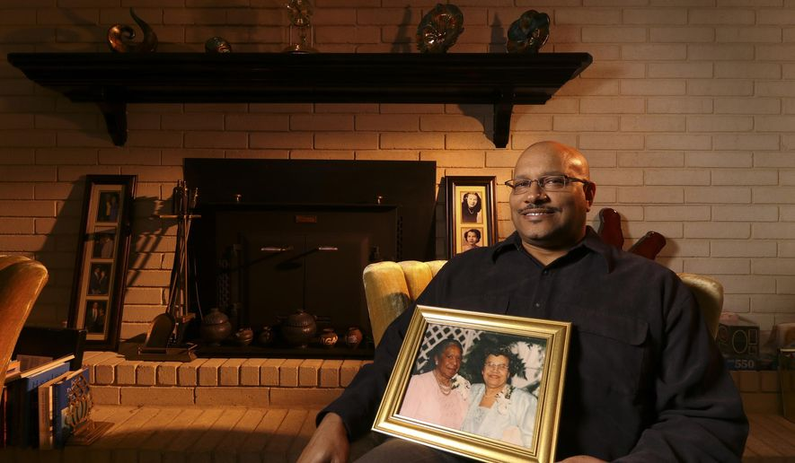 """This photo taken Feb. 27, 2017, shows East Ridge, Tennessee, resident Andre Boaz posing with a portrait of his great-aunt Mary Jackson, left, and mother Aurellia Mitchell Boaz who were both featured in the recent movie """"Hidden Figures"""".(Dan Henry/Chattanooga Times Free Press via AP)"""