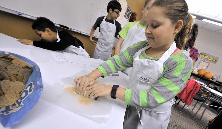 In this Jan. 19, 2017 photo, Maddie Lee, 10, learns to use a can of soup as a rolling pin during the first meeting of the Quick Fixin' Young Chefs Club winter session at the Fort Dodge Middle School, in Fort Dodge, Iowa. The popular club gives students a chance to learn basic cooking skills. (Hans Madsen/The Messenger via AP)