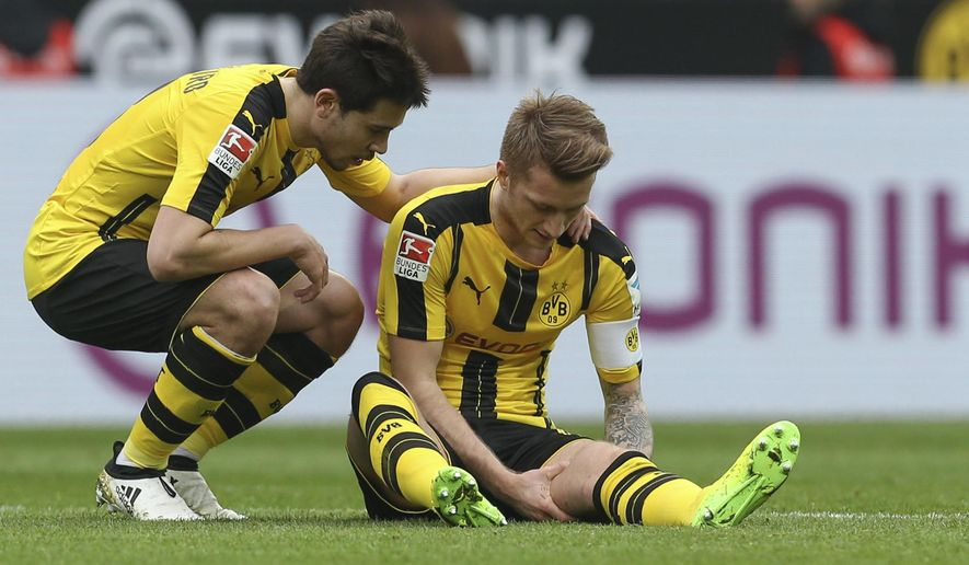 Dortmund's Marco Reus sits injured alongside Raphael Guerreiro, left,  curing the German Bundesliga soccer match between Borussia Dortmund and Bayer Leverkusen, in Dortmund, Germany, Saturday, March 4, 2017.  (Friso Gentsch/dpa via AP)