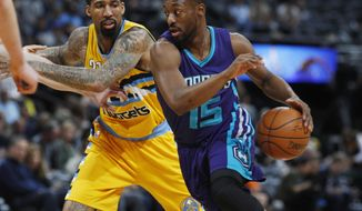 Denver Nuggets forward Wilson Chandler, left, fouls Charlotte Hornets guard Kemba Walker as he drives the lane to the basket in the first half of an NBA basketball game Saturday, March 4, 2017, in Denver. (AP Photo/David Zalubowski)