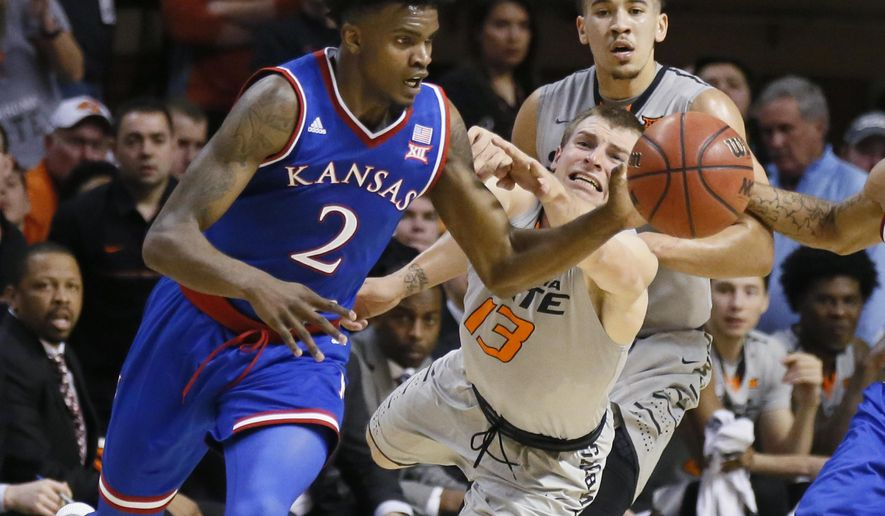 Kansas guard Lagerald Vick (2) reaches a loose ball in front of Oklahoma State guard Phil Forte III (13) in the first half of an NCAA college basketball game in Stillwater, Okla., Saturday, March 4, 2017. (AP Photo/Sue Ogrocki)