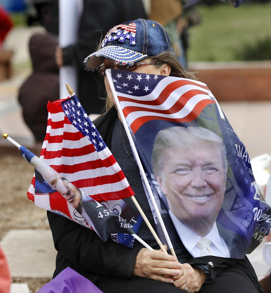 Karen Moseley of Oklahoma City places flags in front of her face to block the chill of the wind while she listens to speakers at the event. Many waving American flags and holding handmade signs expressing pleasure with the new president, supporters of Donald Trump attended a rally Saturday, March 4, 2017, on the south plaza of the state Capitol in Oklahoma City to express their solidarity with him, his administration and his policies. (Jim Beckel/The Oklahoman via AP) **FILE**