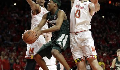 Michigan State guard Cassius Winston, center, shoots between Maryland forwards Justin Jackson, left, of Canada, and Ivan Bender, of Bosnia and Herzegovina, in the first half of an NCAA college basketball game, Saturday, March 4, 2017, in College Park, Md. (AP Photo/Patrick Semansky)