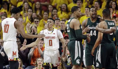 Maryland guard Anthony Cowan (0) high-fives teammate L.G. Gill after Cowan was fouled while shooting in the first half of an NCAA college basketball game against Michigan State, Saturday, March 4, 2017, in College Park, Md. (AP Photo/Patrick Semansky)