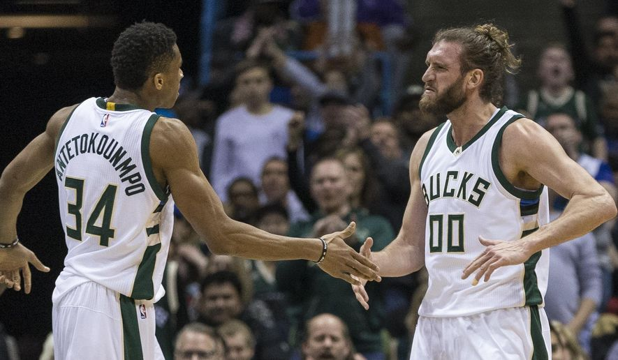 Milwaukee Bucks' Giannis Antetokounmpo, left, slaps hands with teammate Spencer Hawes after Hawes made a basket against the Toronto Raptors during the first half of an NBA basketball game Saturday, March 4, 2017, in Milwaukee. (AP Photo/Tom Lynn)