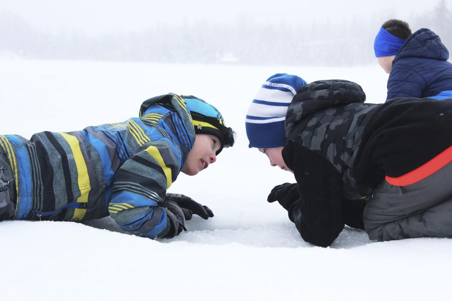 "ADVANCE FOR WEEKEND MARCH 4-5, 2017 AND THEREAFTER - In this Feb. 24, 2017 photo, third grader Ryder Lagerson, left, uses his headlight to help his Kaleidescope School of Arts and Sciences classmate Josiah Holloway, right, try to catch a fish during an ice fishing outing at Sport Lake in Soldotna, Alaska. Hundreds of students from multiple Kenai Peninsula School District schools take part in the Alaska Department of Fish and Game's ""Salmon in the Classroom"" program each year, which includes three ice fishing outings in the winter. (Megan Pacer /Peninsula Clarion via AP)"