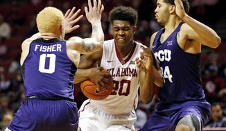 Oklahoma's Kameron McGusty (20) dives between TCU's Jaylen Fisher (0) and Kenrich Williams (34) in the second half of an NCAA college basketball at The Lloyd Noble Center, Saturday,. March 4, 2017 in Norman, Okla. (Steve Sisney/The Oklahoman via AP)