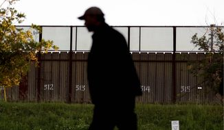 A man passes a section of border fencing that separates Tijuana, Mexico, with San Diego. (Associated Press)