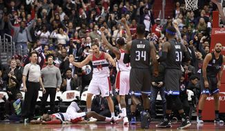 Washington Wizards guard Bojan Bogdanovic (44) reacts with Wizards guard John Wall (on floor)and guard Bradley Beal (3) after an NBA basketball game as Orlando Magic forward Jeff Green (34), forward Terrence Ross (31) and guard Evan Fournier (10), of France, (10) look on Sunday, March 5, 2017, in Washington. (AP Photo/Nick Wass)