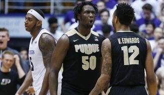 Purdue forward Caleb Swanigan (50) celebrates with forward Vincent Edwards (12) after scoring a basket as Northwestern center Dererk Pardon reacts as he walks to the bench during the second half of an NCAA college basketball game, Sunday, March 5, 2017, in Evanston, Ill. Purdue won 69-65. (AP Photo/Nam Y. Huh) **FILE**