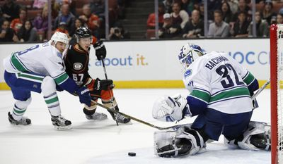 Vancouver Canucks goalie Richard Bachman, right, makes a save as teammate Christopher Tanev, left, and Anaheim Ducks' Rickard Rakell, of Sweden, watch during the second period of an NHL hockey game, Sunday, March 5, 2017, in Anaheim, Calif. (AP Photo/Jae C. Hong)