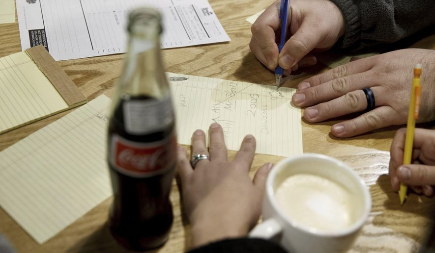 In this Wednesday, Jan. 11, 2017 photo, team members write down their guesses for answers as people participate in Trivia Mafia, in Omaha, Neb. (Sarah Hoffman/Omaha World-Herald via AP)