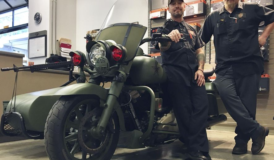 "In this Feb. 22, 2017 photo, Jeremy Taylor, left and Chase Wainwright were among the technicians who helped build the World War II-themed motorcycle at the Harley-Davidson dealership in Tallahassee, Fla. The motorcycle looks reminiscent of vehicles on the set of the 1998 World War II classic movie like ""Saving Private Ryan,"" with that distinct shade of green and black accents.(Nada Hassanein/Tallahassee Democrat via AP)"