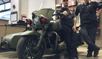 """In this Feb. 22, 2017 photo, Jeremy Taylor, left and Chase Wainwright were among the technicians who helped build the World War II-themed motorcycle at the Harley-Davidson dealership in Tallahassee, Fla. The motorcycle looks reminiscent of vehicles on the set of the 1998 World War II classic movie like """"Saving Private Ryan,"""" with that distinct shade of green and black accents.(Nada Hassanein/Tallahassee Democrat via AP)"""