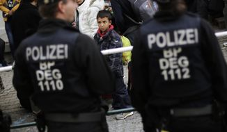 A young boy looks at police officers after he and other migrants were pulled out of a train by German Federal Police at the train station of the southern German border town Passau, Sept. 16, 2015. (AP Photo/Markus Schreiber) ** FILE **