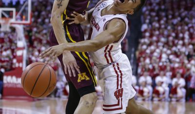 Wisconsin's D'Mitrik Trice, right, runs into Minnesota's Amir Coffey (5) during the first half of an NCAA college basketball game Sunday, March 5, 2017, in Madison, Wis. (AP Photo/Andy Manis)