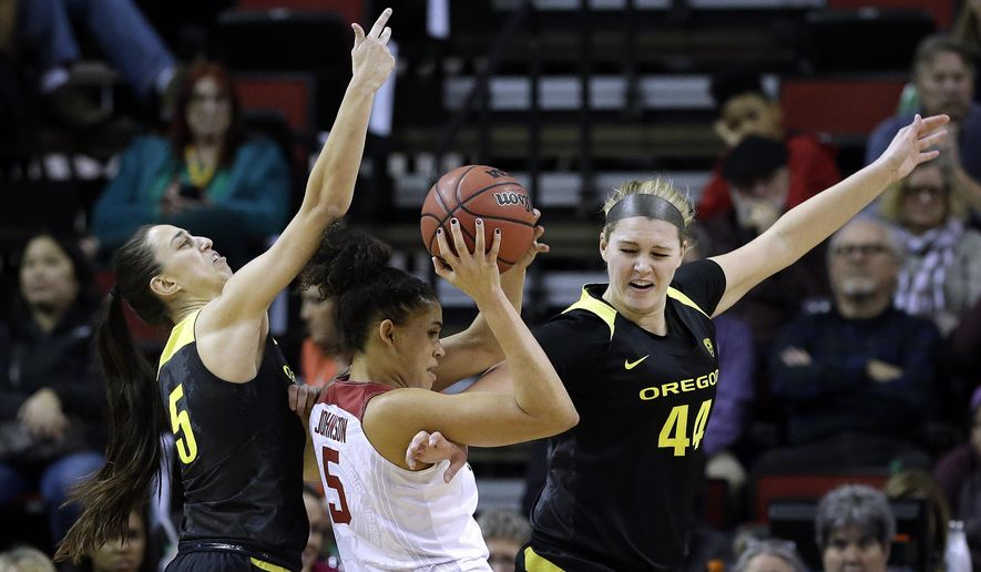 Stanford's Kaylee Johnson, center, is defended by Oregon's Maite Cazorla, left, and Mallory McGwire during the first half of an NCAA college basketball game in the Pac-12 tournament, Saturday, March 4, 2017, in Seattle. (AP Photo/Elaine Thompson)