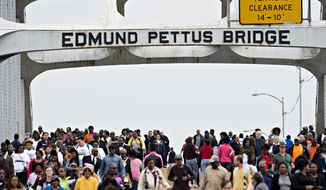"People walk over the Edmund Pettus Bridge towards Selma, Ala., during the annual re-enactment of a key event in the civil rights movement Sunday, March 5, 2017. Sunday marked the 52nd anniversary of the march across the Edmund Pettus Bridge over the Alabama River in Selma. On March 7, 1965, African-Americans seeking voting rights launched a march across the bridge en route to Montgomery but were attacked by police. That violent episode became known as ""Bloody Sunday."" (Albert Cesare/The Montgomery Advertiser via AP)"