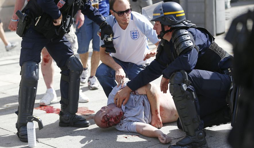 FILE - In this Saturday, June 11, 2016 file photo, a man injured in clashes is assisted by police officers in downtown Marseille, France. New FIFA secretary general Fatma Samoura says extra security measures are planned for the 2018 World Cup in Russia following hooligan violence at the European Championship. (AP Photo/Darko Bandic, File)