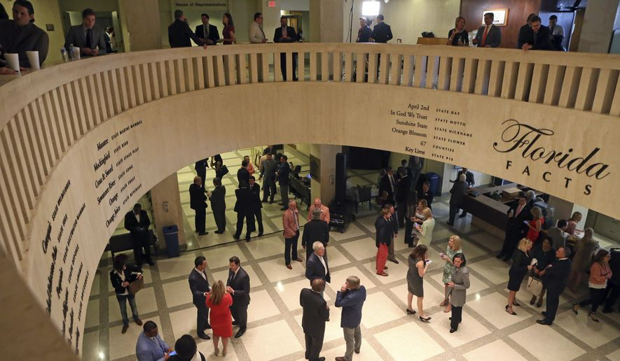"FILE- In this March 11, 2016 file photo, people gather during the legislative session in Tallahassee, Fla.  The Florida Society of Newspaper Editors is creating a ""scorecard"" for state lawmakers on where they stand on keeping records public, tracking public records bills and amendments they sponsor and how they vote. For Florida's legislative session opening Monday, March 6, 2017,  the state's First Amendment Foundation is drafting a priority list of bills, including exemptions aimed at making it more difficult to obtain public records. Reporters will grade lawmakers based on the scorecard after the session. (AP Photo/Steve Cannon, File)"