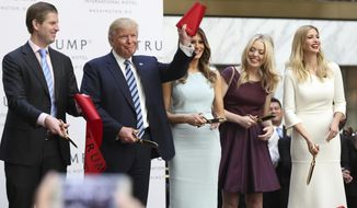 FILE - In this Oct. 26, 2016 file photo, then-Republican presidential candidate Donald Trump, together with his family, from left, Eric Trump, Melania Trump, Tiffany Trump and Ivanka Trump, waves part of a ribbon after cutting the ribbon during the grand opening of Trump International Hotel in Washington. Trump's $200 million hotel inside the federally owned Old Post Office building has become the place to see, be seen, drink, network, even live, for the still-emerging Trump set. It's a rich environment for lobbyists and anyone hoping to rub elbows with Trump-related politicos, despite the veil of ethics questions that hangs overhead.  (AP Photo/Manuel Balce Ceneta, File)