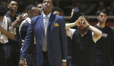 Wake Forest head coach Danny Manning and his bench react to a three-point basket by Bryant Crawford during the second half of an NCAA college basketball game against Virginia Tech, Saturday, March 4, 2017 in Blacksburg Va. (Matt Gentry/The Roanoke Times via AP)