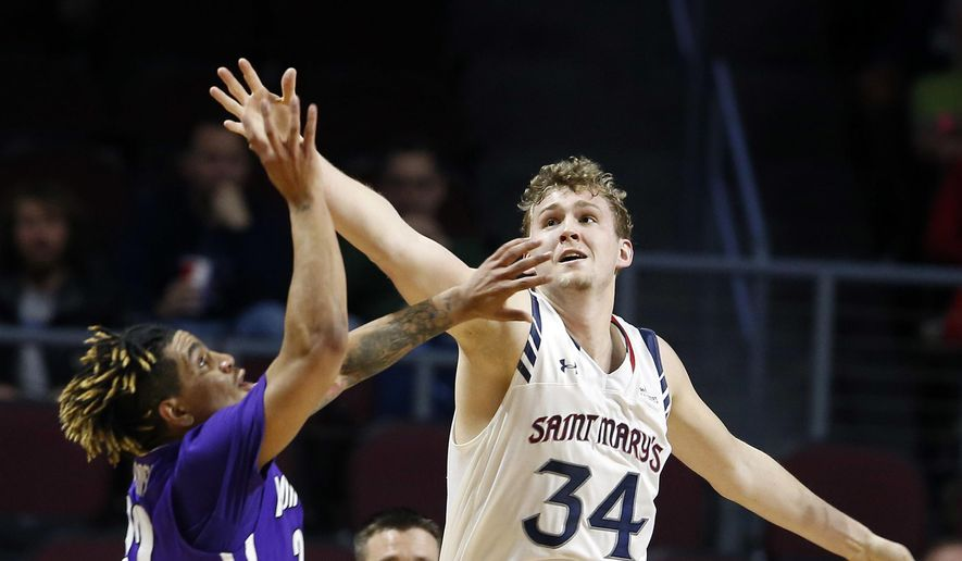 Portland's Jazz Johnson, left, and Saint Mary's Jock Landale reach for the ball during the first half of a West Coast Conference tournament NCAA college basketball game Saturday, March 4, 2017, in Las Vegas. (AP Photo/Isaac Brekken)