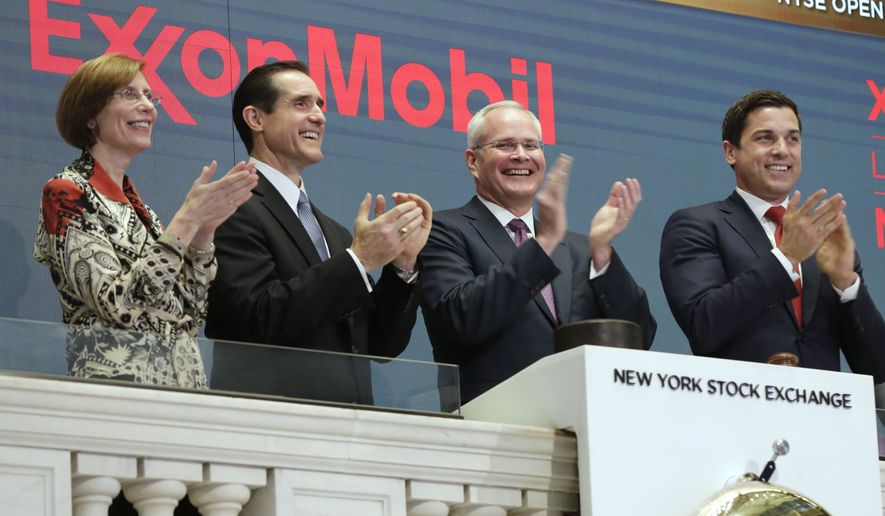 In this Wednesday, March 1, 2017, file photo, Exxon Mobil Corporation Chairman & CEO Darren Woods, third from left, joins the applause during opening bell ceremonies at the New York Stock Exchange. Woods succeeded Rex Tillerson, following Tillerson's nomination by President Donald Trump to be the next United States Secretary of State. Woods is a veteran of the more cautious refining side of the oil business who is likely to focus relentlessly on controlling costs. (AP Photo/Richard Drew, File)