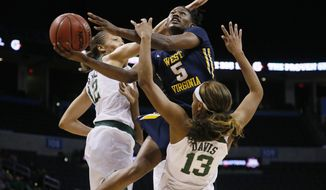 West Virginia guard Tynice Martin (5) shoots between Baylor guard Alexis Prince (12) and forward Nina Davis (13) in the first half of an NCAA college basketball championship game at the Big 12 Conference tournament in Oklahoma City, Monday, March 6, 2017. (AP Photo/Sue Ogrocki)
