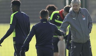 Arsenal's Alexis Sanchez, left, shakes hands with manager Arsene Wenger during a training session at the Arsenal Training Centre, London Colney, London Monday March 6, 2017.  Arsenal star striker Sanchez was dropped from Arsenal's starting line-up for their 3-1 defeat to Liverpool on Saturday. (Tim Goode/PA via AP)