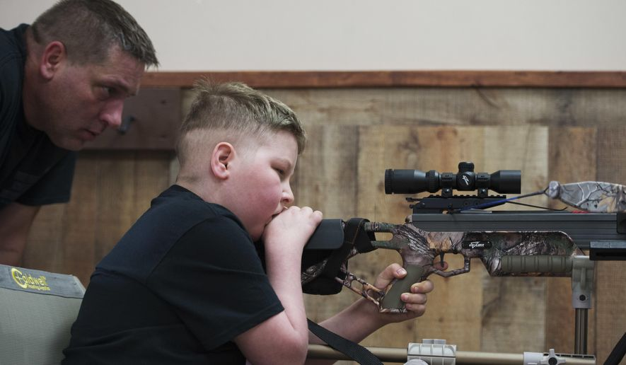 In a Friday, Feb. 24, 2017 photo, Bill Kohler watches over his son Ayden's shoulder as he shoots a target at X-Treme Archery in Springettsbury Township, Pa. Ayden was practicing for an upcoming hog and ram hunt. Though cancer has limited his mobility, a special chair with an extended arm helps stabilize the bow so Ayden can still shoot. (Kate Penn /York Daily Record via AP)