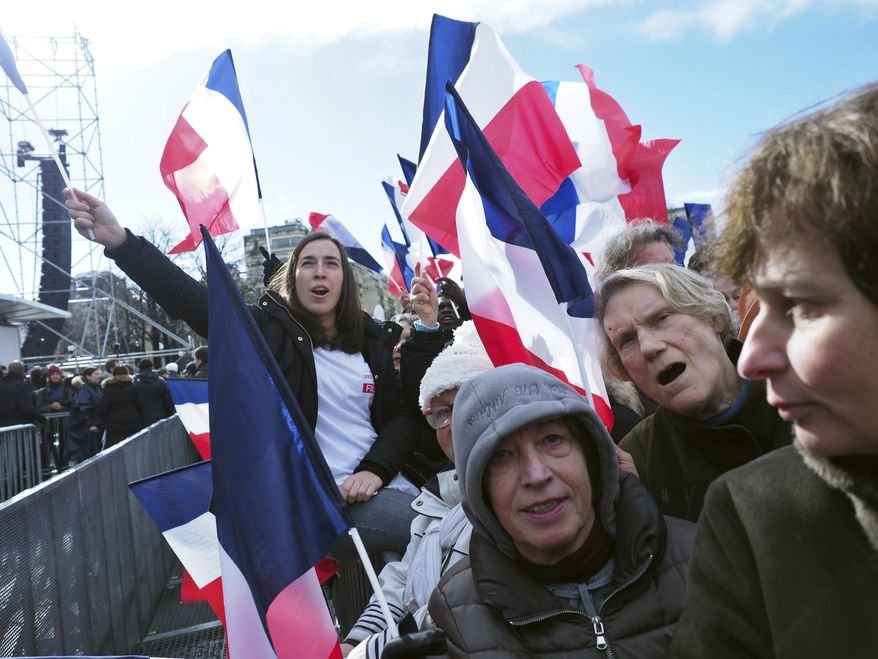 Supporters of conservative presidential candidate Francois Fillon waves French flag, during a rally in Paris, Sunday, March 5, 2017. The rally across from the Eiffel Tower is meant to gauge Fillon's remaining support after numerous defections by conservative allies just seven weeks before the first round of the April-May election. Fillon faces corruption charges. (AP Photo/Thibault Camus)