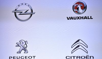 The logos of car makers : Opel, Vauxhall, Peugeot and Citroen are displayed during a press conference held in Paris, France, Monday, March 6, 2017. General Motors is selling its loss-making European car business, including Germany's Opel and British brand Vauxhall, to France's PSA group in a deal that realigns the industry in the region. (AP Photo/Zacharie Scheurer)