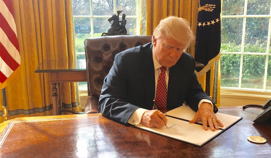 President Trump signs a revised travel ban on March 6 that temporarily halts entry to the U.S. for people from six Muslim-majority nations who are seeking new visas, allowing those with current visas to travel freely. (White House)