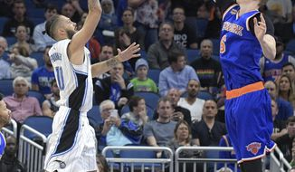 Orlando Magic guard Evan Fournier (10) puts up a shot in front of New York Knicks forward Kristaps Porzingis (6) during the first half of an NBA basketball game in Orlando, Fla., Monday, March 6, 2017. (AP Photo/Phelan M. Ebenhack)