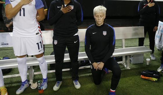 """FILE - In this Sunday, Sept. 18, 2016 file photo, United States' Megan Rapinoe, right, kneels next to teammates Ali Krieger (11) and Crystal Dunn (16) as the U.S. national anthem is played before an exhibition soccer match against Netherlands in Atlanta. Megan Rapinoe says she will respect a new U.S. Soccer Federation policy that says national team players """"shall stand respectfully"""" during national anthems. The policy was approved last month but came to light Saturday, March 4, 2017 before the U.S. women's national team lost to England in a SheBelieves Cup match. (AP Photo/John Bazemore, File) **FILE**"""