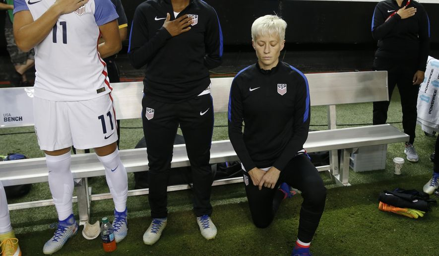 8630654efc0 18, 2016 file photo, United States' Megan Rapinoe, right, kneels next to  teammates Ali Krieger (11) and Crystal Dunn (16) as the U.S. national  anthem is ...