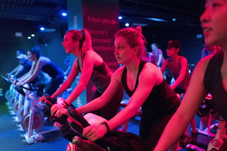 In this March 1, 2017, file photo, women wear Fitbit's new Alta HR on their wrist while working out at a Swerve fitness center in New York. Fitbits already track how much people sleep and use sensors to measure periods of being awake or restless while in bed. Now, using a built-in heart-rate monitor, the devices will break sleep into clinically defined stages. (AP Photo/Mark Lennihan) ** FILE **