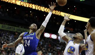 Atlanta Hawks' Kent Bazemore, left, reaches for a ball against Golden State Warriors' David West in the second quarter of an NBA basketball game in Atlanta, Monday, March 6, 2017. (AP Photo/David Goldman)
