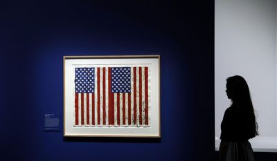 "A British Museum representative poses for photographs next to ""Flag I"" by Jasper Johns which features in ""The American Dream: pop to the present"" exhibition during a media photocall at the British Museum in London, Monday, March 6, 2017. The exhibition, which opens to the public from March 9 and runs until June 18, charts modern and contemporary print making. (AP Photo/Matt Dunham)"