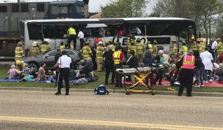 Emergency personnel assist injured passengers after their charter bus collided with a train in Biloxi, Miss., Tuesday, March 7, 2017.  Biloxi city spokesman Vincent Creel says emergency responders were still removing injured people from the bus more than 30 minutes after the crash (John Fitzhugh/Sun Herald via AP)