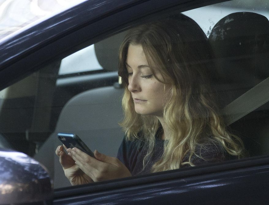 FILE - In this Wednesday, June 22, 2016, file photo, a driver uses her mobile phone while sitting in traffic in Sacramento, Calif. A measure to ban holding a phone while driving passed in the Washington state House a day after a similar measure passed in the Senate. (AP Photo/Rich Pedroncelli, File)
