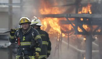 Philadelphia firefighters walk past a blaze at the PECO electrical substation in the Nicetown-Tioga neighborhood, Tuesday, March 7, 2017, in Philadelphia. Tens of thousands of electric customers were reported to be without power as fire crews battled a blaze at a north Philadelphia utility substation. (AP Photo/Matt Slocum)