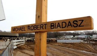 """ADVANCE FOR MONDAY MARCH 13 AND THEREAFTER - An engraved wooden cross stands as a memorial near the spot where Mike Biadasz, 29, was found dead in August 2016 on his family's farm in Amherst, Wis., after he was overcome by gases from a manure pit. Bob and his wife, Diane, always expected Mike would someday take over the family farm. Now, the words he lived by can be read on a pair of signs placed on the farm: """"Live today like you are going to die tomorrow, but farm today like you are going to farm forever.""""  (Chris Mueller/The Stevens Point Journal via AP)"""