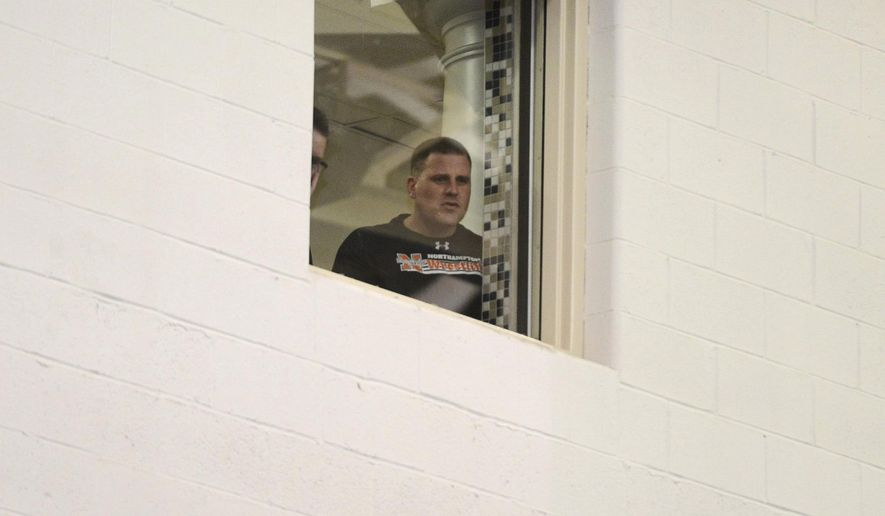 "ADVANCE FOR RELEASE SATURDAY, MARCH 11, 2017, AT 3:01 A.M. EST. AND THEREAFTER - In this March 3, 2017 photo, Kevin Fenstermacher watches his son compete in wrestling tournament from a quiet room at Liberty High School in Bethlehem, Pa. The father quietly watched his son win his quarterfinal wrestling tournament match, alone but for a security guard in a section carved out for him in a legal settlement after he was banned due to ""offensive behavior"" at a previous match. Misbehaving fans are a constant in sports and the Lehigh Valley is no exception. (Chris Shipley/The Morning Call via AP)"