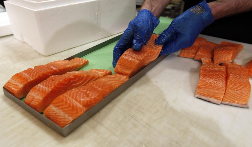 """In this Friday, April 10, 2015 photo, Canadian certified organic farm-raised King Salmon filets are placed on a tray in a store in Fairfax, Va. Overeating or under-eating 10 foods and nutrients contributes to nearly half of U.S. deaths from heart disease, strokes and diabetes, a study released on Tuesday, March 7, 2017, suggests. """"Good"""" foods that were under-eaten include: nuts and seeds, seafood rich in omega-3 fats including salmon and sardines; fruits and vegetables; and whole grains. (AP Photo/Alex Brandon)"""